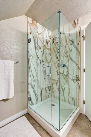 renovated: Photo of attic bathroom with an alcove shower, marble tile wall trim and glass door. Northwest, USA