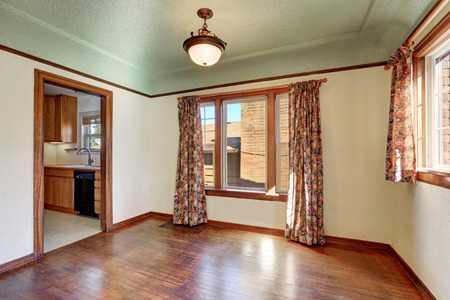 tudor: Empty room interior of tudor style home with colorful window curtains and hardwood floor. Northwest, USA