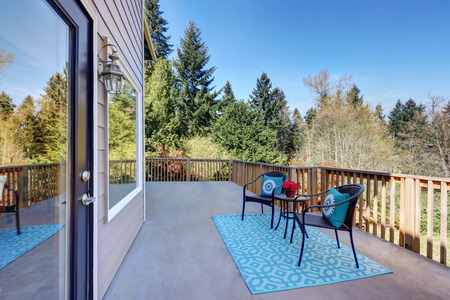 View of second floor deck finished with wooden railings.  Also outdoor chairs accented with blue pillows paired with geometric pattern rug. Northwest, USA