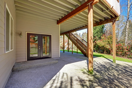 second floor: Backyard view of two story house with concrete floor, double door, and  staircase to second floor deck. Northwest, USA Stock Photo