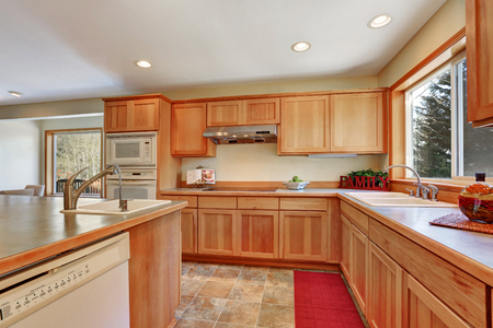 Kitchen interior with honey cabinets , built-in appliances and large kitchen island. Northwest, USA