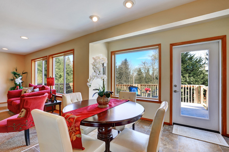 Open concept dining room with round solid wood table and white leather chairs. Northwest, USA