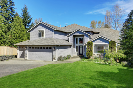 Traditional blue home exterior in Puyallup with wood siding and elegant front door. Northwest, USA Stok Fotoğraf