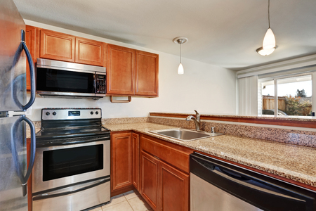 countertop: Small kitchen features shaker cabinets paired with granite countertop. Northwest, USA