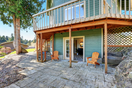 second floor: Backyard view of waterfront home with green siding and wraparound deck on the second floor. Northwest, USA Stock Photo