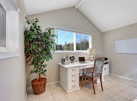 Home office interior filled with white desk with drawers, chair and green decorative tree in a pot. The room features vaulted ceiling and tiled floor. Northwest, USA