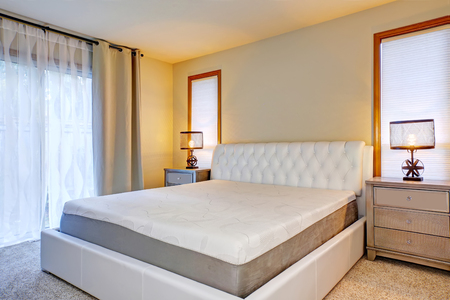 bedside tables: White double bed front view, with two lamps on bedside tables. Northwest, USA Stock Photo