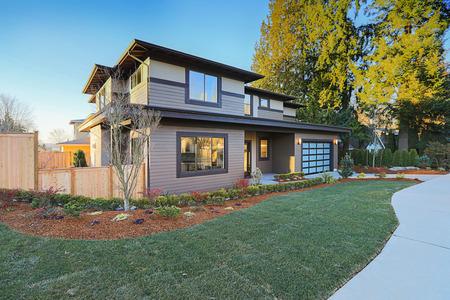 Nuevo exterior casero de la construcción con plan de casa contemporáneo cuenta con techo de pendiente baja, los revestimientos de marrón y la puerta del garaje de vidrio. Noroeste, EE.UU.