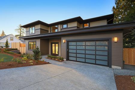 Nuevo exterior casero de la construcción con plan de casa contemporáneo cuenta con techo de pendiente baja, los revestimientos de marrón y la puerta del garaje de vidrio. Noroeste, EE.UU. Foto de archivo