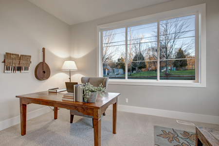 Interior of home office with soft gray walls features Wood desk with gray wingback chair, large window and decorative vintage musical instruments on the wall. Northwest, USA