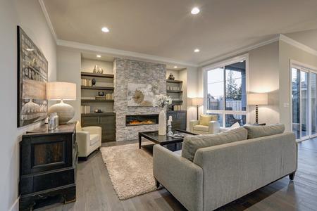 Salon intérieur dans des couleurs grises et brunes dispose gris canapé au-dessus des planchers de bois sombre face cheminée en pierre avec des étagères. Northwest, États-Unis Banque d'images - 70205140