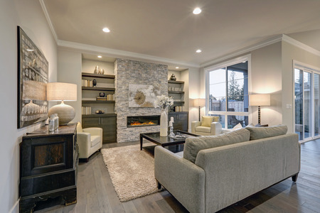 Woonkamer interieur in grijze en bruine kleuren beschikt over grijze bank bovenop donkere hardhouten vloeren met stenen open haard met ingebouwde planken. Noordwest, Verenigde Staten