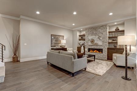 組み込みの棚に石造りの暖炉に直面して暗い堅木張りの床の上にグレーと茶色の色グレー機能ソファのリビング ルームのインテリア。米国北西部