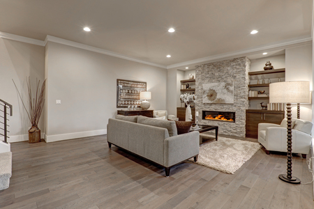 Living room interior in gray and brown colors features gray sofa atop dark hardwood floors facing stone fireplace with built-in shelves. Northwest, USA  免版税图像