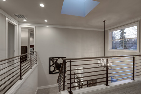 second floor: Second floor landing in gray tones features skylight over the staircase with metal horizontal railings. Northwest, USA