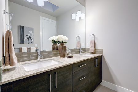 Grijs en schoon badkamerontwerp in gloednieuw huis met dubbele wastafel ijdelheid met donkere houten kasten, granieten aanrecht en glazen taupe backsplash. Northwest, VS.