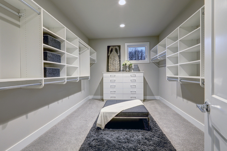 remodeled: Huge walk-in closet with shelves, drawers and gray bench. Northwest, USA  Stock Photo