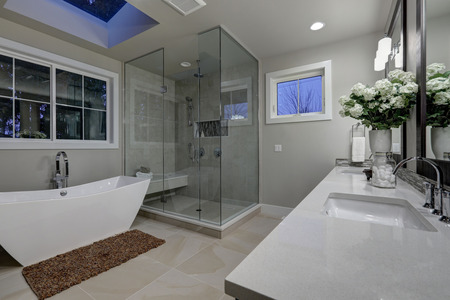 Amazing gray master bathroom with large glass walk-in shower, freestanding tub and skylights on the ceiling. Northwest, USA