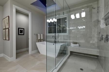 Increíble gris baño principal con vidrio de gran cabina de ducha, bañera independiente y claraboyas en el techo. Noroeste, EE.UU. Foto de archivo