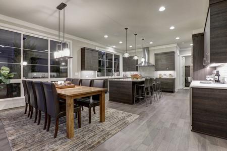 Luxe nieuwbouw huis met open plattegrond: eetkamer en keuken design. Rustieke houten eettafel overeenkomt met een moderne stijl lederen stoelen. Keuken geaccentueerd met donkere kasten. Northwest, USA