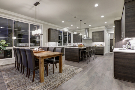 Luxury New construction home with open floor plan: dining and kitchen design. Rustic wood dining table matches with modern style leather chairs. Kitchen accented with dark cabinetry. Northwest, USA 免版税图像