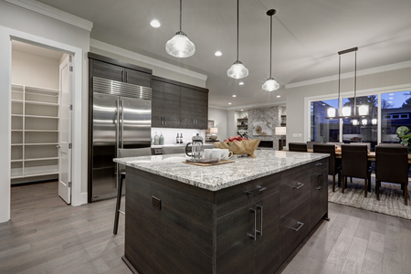 large: Modern open plan gray kitchen features dark gray cabinets paired with granite countertops. Open door to a pantry. Northwest, USA  Stock Photo