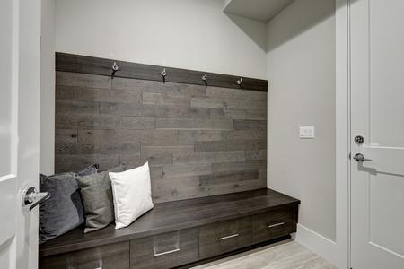 グレー ロビー機能半分木の板のアクセント壁内蔵ストレージ ベンチ グレーと白の枕をトッピングします。米国北西部 写真素材