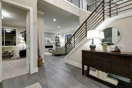 Open plan entryway in new construction home features console table with drawers , staircase with metal railings and dark hardwood floors. Northwest, USA