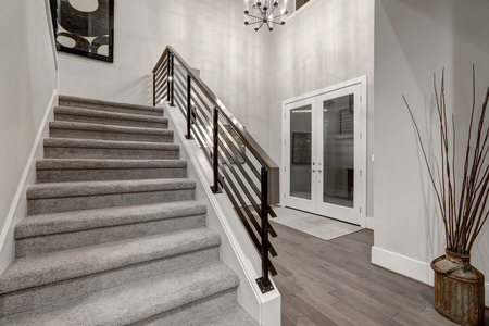 Two story foyer in new construction home boasting staircase with metal railings and dark hardwood floors. Northwest, USA Stock Photo