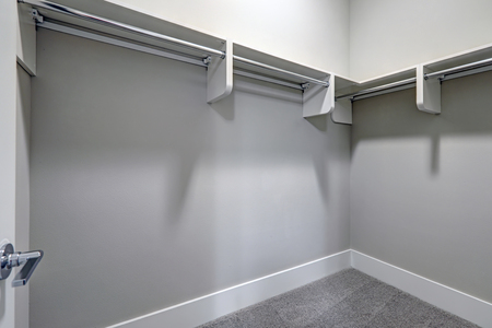 Empty walk-in closet with pale gray walls paint color and carpet floor. Northwest, USA