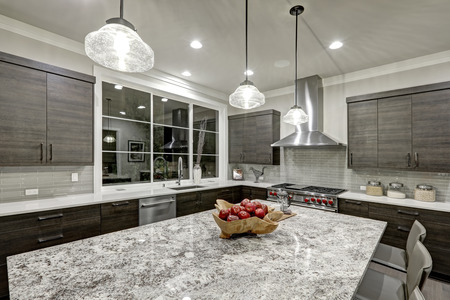 Modern, traditioneel keukenontwerp in een nieuw, luxe huis met donkergrijze kasten, wit kwarts en granieten werkbladen, glanzende grijze lineaire tegeltablenspanning en groot kookeiland. Northwest, VS.