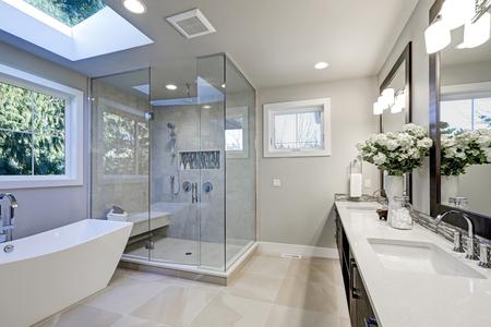 Ruime badkamer in grijstinten met vloerverwarming, vrijstaand bad, inloopdouche, dubbele wastafel en dakramen. Northwest, USA