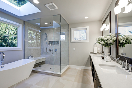 Spacious bathroom in gray tones with heated floors, freestanding tub, walk-in shower, double sink vanity and skylights. Northwest, USA Banco de Imagens - 70106274