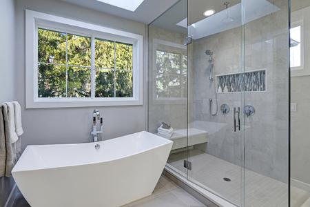 Glazen inloopdouche met grijze metrotegel betegelde rand en witte vrijstaande kuip in nieuwe luxe huisbadkamer. Northwest, VS.