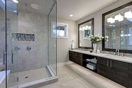 Spacieuse salle de bains dans les tons gris avec plancher chauffant, douche à l'italienne, double vasque et puits de lumière Nord-ouest, États-Unis