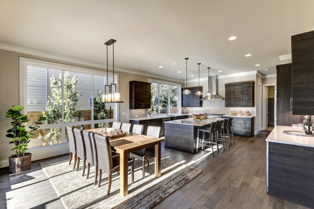 open floor plan: Luxury New construction home with open floor plan: dining and kitchen design. Rustic wood dining table matches with leather chairs. Kitchen accented with dark cabinetry. Northwest, USA Stock Photo