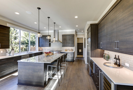 Modern gray kitchen features dark gray flat front cabinets paired with white quartz countertops and a glossy gray linear tile backsplash. Bar style kitchen island with granite counter. Northwest, USA Foto de archivo