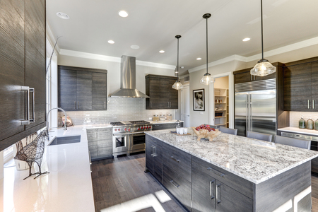 Modern gray kitchen features dark gray flat front cabinets paired with white quartz countertops and a glossy gray linear tile backsplash. Bar style kitchen island with granite counter. Northwest, USA  Stock Photo