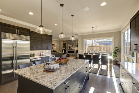 Modern gray kitchen features  dark gray cabinetry paired with white quartz countertops and a glossy gray linear tile backsplash. Bar style kitchen island with granite counter. Northwest, USA  Stockfoto
