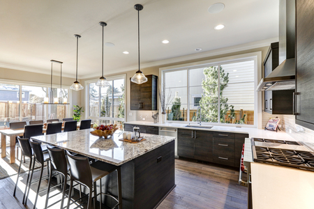 Modern gray kitchen features dark gray flat front cabinets paired with white quartz countertops and a glossy gray linear tile backsplash. Bar style kitchen island with granite counter. Northwest, USA Standard-Bild