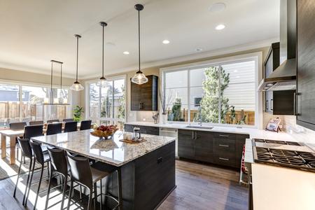 Moderne grijze keuken is voorzien van donkergrijze vlak front kasten gecombineerd met witte kwarts werkbladen en een glanzend grijs lineaire tegel backsplash. Bar stijl kookeiland met granieten aanrechtblad. Northwest, USA
