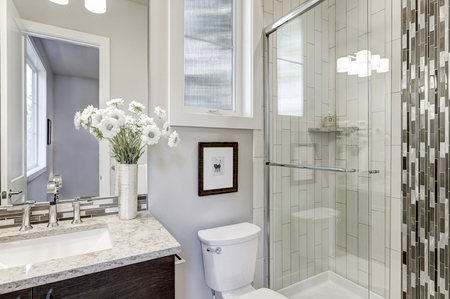 Glass walk-in shower with white subway tiled surround accented with vertical mosaic tile strip in new luxury home bathroom. Northwest, USA