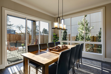 Sun filled dining room in new luxury home boasts Rustic wood dining table with leather chairs surrounded by sliding glass doors which lead out to the patio. Northwest, USA