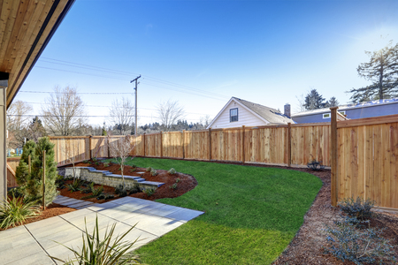 wooden fence: Sloped backyard surrounded by wooden fence. Exterior of New Luxury  home with tiled walkway and green lawn. Northwest, USA