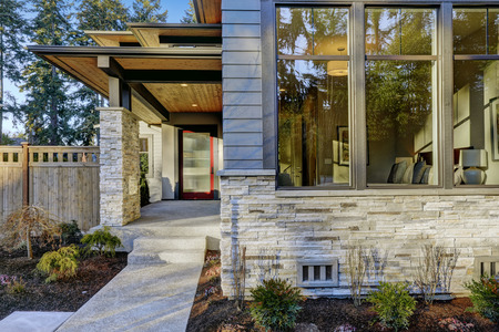 Entrance of  Luxurious new construction home with blue siding and stone decor. Concrete walkway lead to long covered porch with modern glossy front door. Northwest, USA