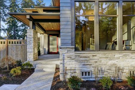 Entree van luxe nieuwbouw huis met blauwe gevelbeplating en steen decor. Concrete loopbrug leiden tot lange overdekte veranda met moderne glossy voordeur. Northwest, USA