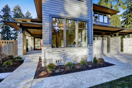 walkway: Entrance of  Luxurious new construction home with blue siding and stone decor. Concrete walkway lead to long covered porch with modern glossy front door. Northwest, USA