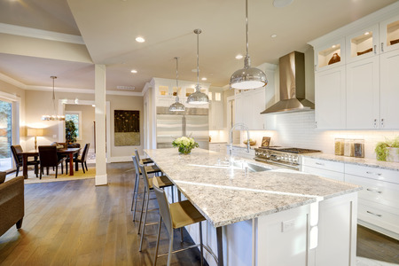 White kitchen design features large bar style kitchen island with granite countertop illuminated by modern pendant lights. Northwest, USA Archivio Fotografico