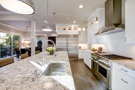 白いキッチン デザイン機能の広いモダンなペンダント ライトに照らされた花こう岩のカウンター トップのスタイル キッチン島バー。白いシェーカ