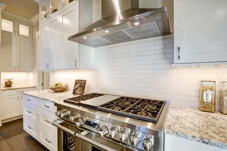 Beautiful kitchen features a nook filled with stainless steel stove, hood, white subway tile backsplash paired with granite countertops. Northwest, USA 免版税图像